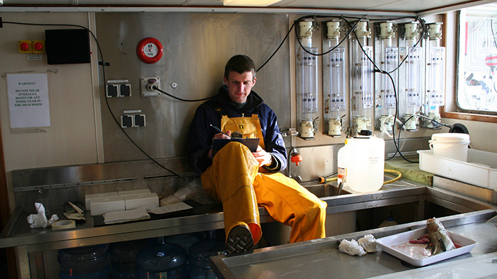 Scientist sitting in a laboratory on  a research vessel making notes on a clipboard.