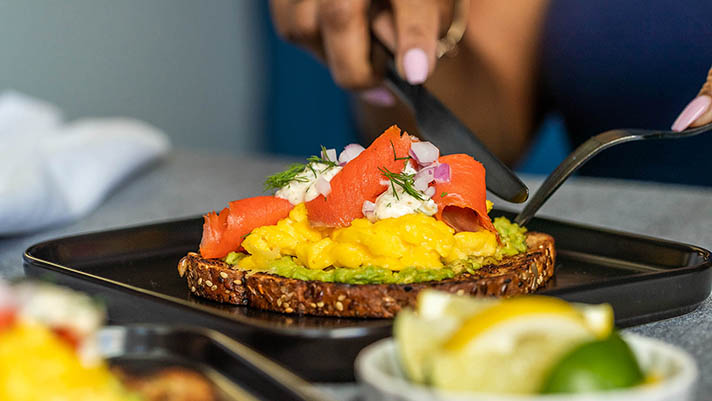 Hands with cutlery cutting into smoked salmon and scrambled eggs on toast