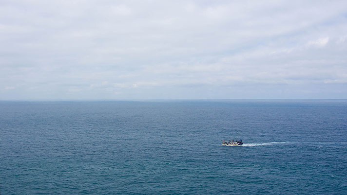 Traditional fishing boat in the sea seen from a distance with blue sea and sky