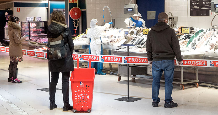 Backs of shoppers in masks at supermarket fresh fish counter