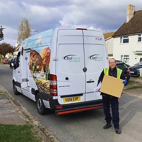 Man in hi-vis jacket holding a cardboard box by back doors of delivery van
