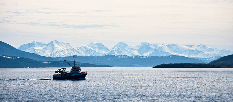 Fishing boat on still water with snow-capped mountains behind