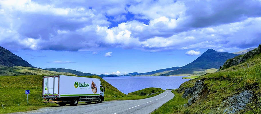 Delivery van parked on winding road, surrounded by water and hills