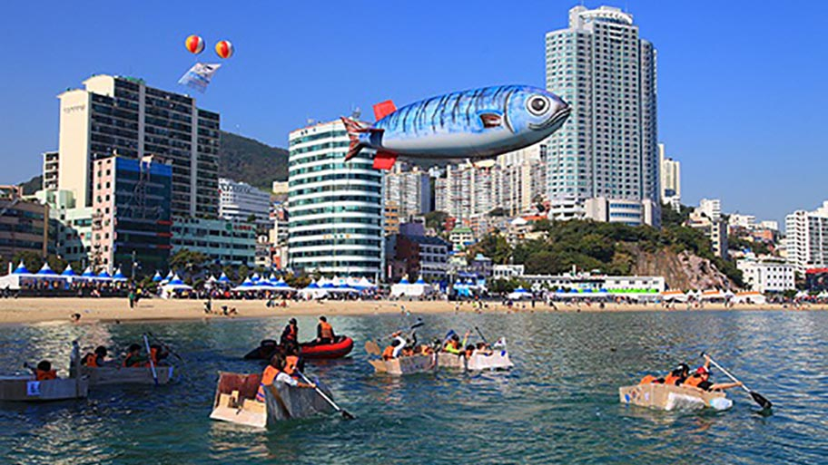 People in small rowing boats with inflatable mackerel above and buildings behind
