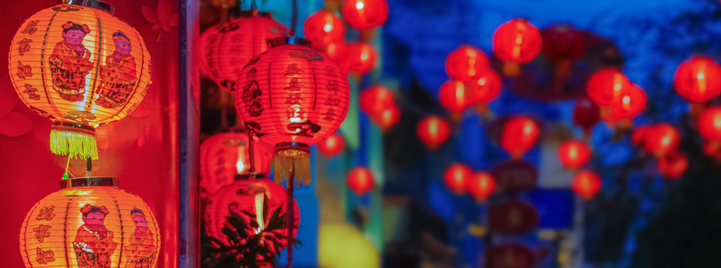 Red Chinese New Year lanterns hanging on a wall.