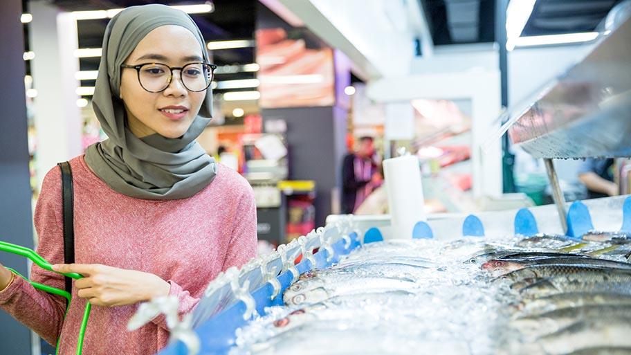 Woman wearing a hijab at fish counter