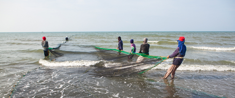 Filipino fishers with a net on the shore.