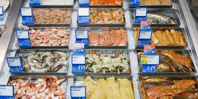 A cold food storage counter with seafood.