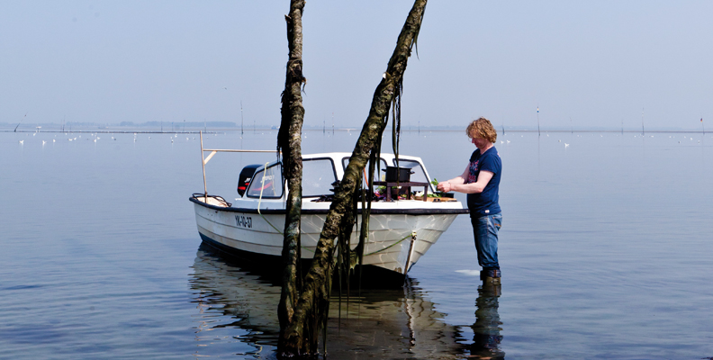 Bart van Olphen standing in the shores with a boat.