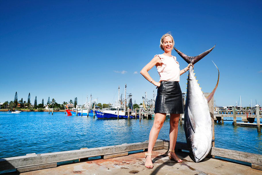 Woman holding large tuna at dock with boats docked and blue sky