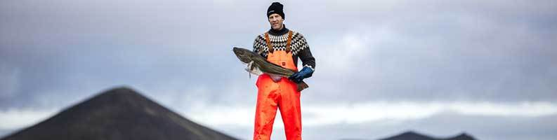 Páll Hreinn Pálsson holding a cod with mountains in the background.
