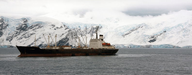A krill boat floating in the sea in the Antarctic near snowy mountains.