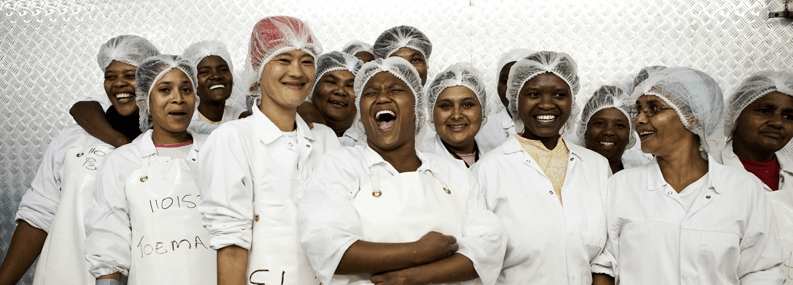 A group of individuals with hairnets and in white aprons laughing and smiling.