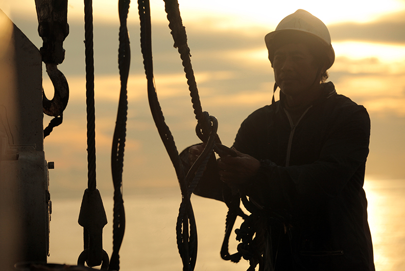 A sailor with a helmet adjusting ropes on a boat.