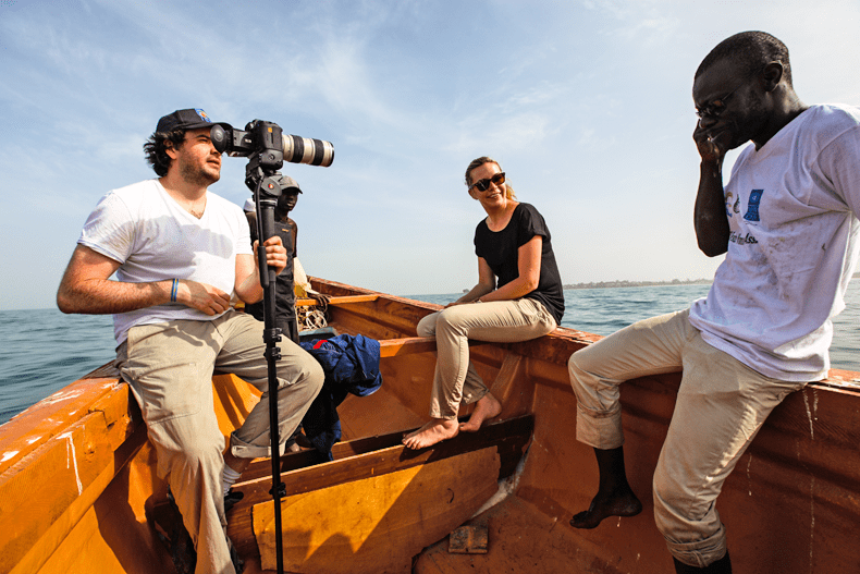 Three people on a boat in Gambia, one with a camera.