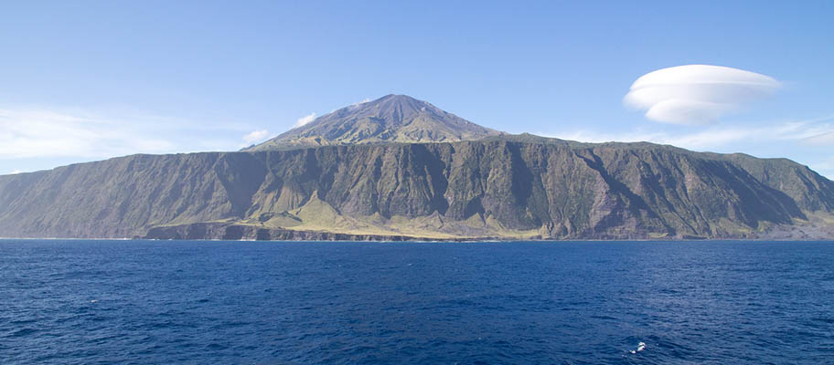 Island of Tristan da Cunha with clouds above and sea in foreground
