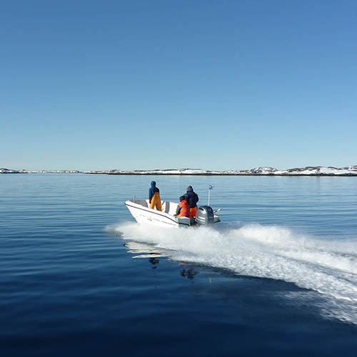 Small two-person motor boat on calm water moving away from camera