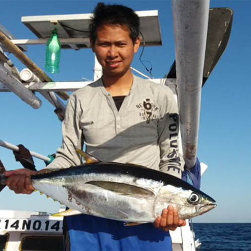 Young man holding large tuna fish on boat