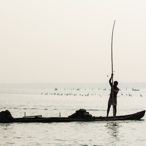 Ashtamudi Estuary short-necked clam fisherman in a boat