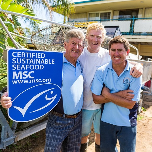 Group photo of Damien Bell (right) and fishers holding MSC blue label placard