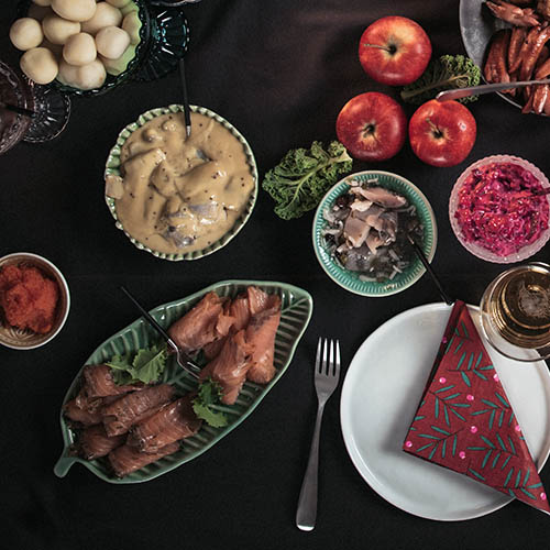 Scandinavian Christmas table seen from above with salmon and herring dishes