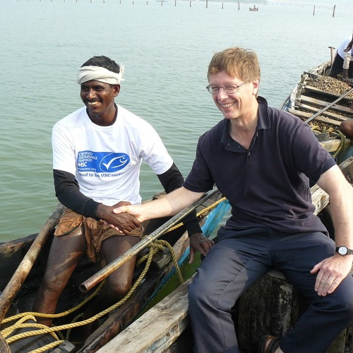 A clam fisherman (left) in a docked canoe shaking hands with David Agnew (right)