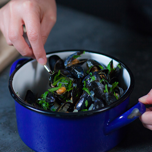 Person's hands stirring a pot of ready-to-serve mussels with a spoon