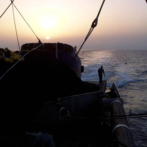 Silhouette of fishing gear and man on deck of large ship at sea facing setting sun