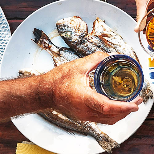 Vertical top view on table with grilled fish and hands with clinking goblets stock photo