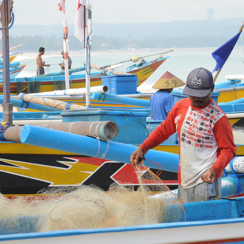Fisherman gathering nets among colourful boats