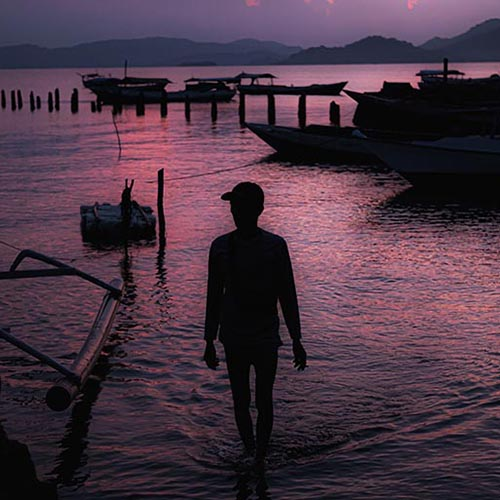 Silhouette of man at dusk looking out over small fishing boats on water