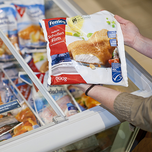 Close-up of person's hands holding MSC certified frozen fish product over seafood filled freezer