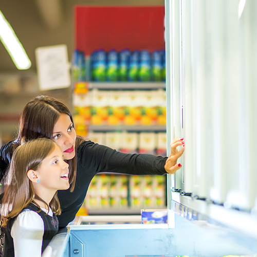 Woman and daughter choosing from frozen section in supermarket