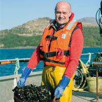 Man holding MSC certified mussels on board  boat as part of Lidl campaign