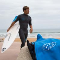 Aritz Aranburu on beach holding surfboard with MSC branded jacket in foreground