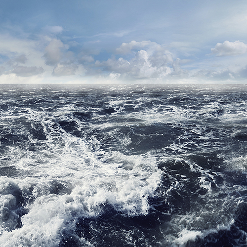 Dark stormy ocean waves with a clear blue cloudy sky