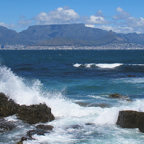 Long shot of waves crashing against rocks in front of Cape Town