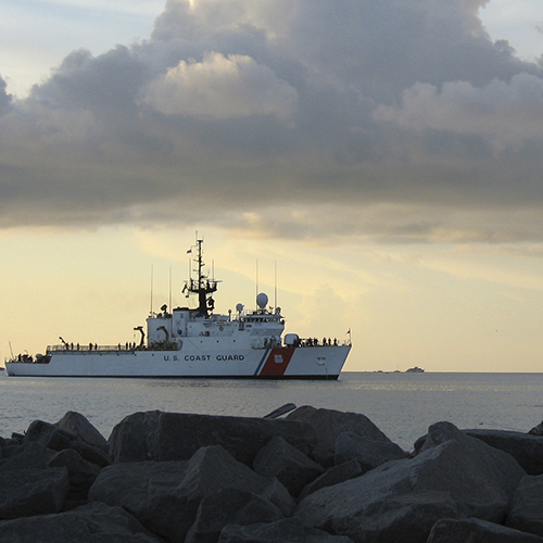 Coastguard ship (left) out on the ocean, foregrounded by rocks and under a cloudy sky