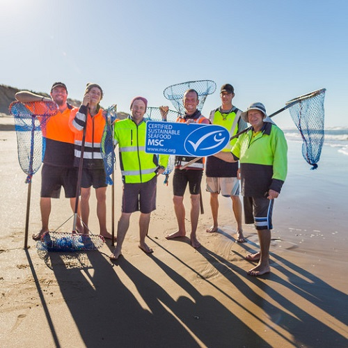 Group of fishers holding nets and an MSC placard on the beach