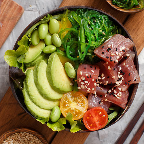 Tuna sashimi, avacado and vegetables in bowl, aerial view