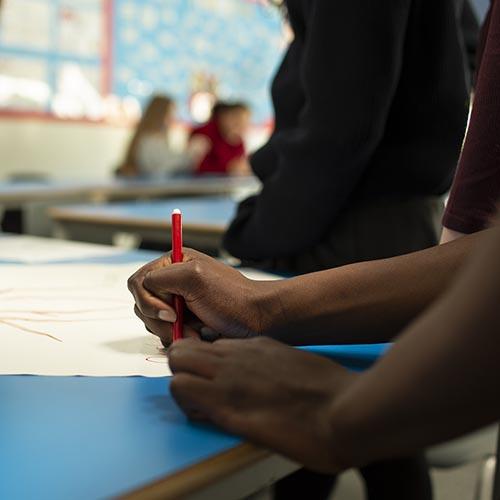 Hands on school desk, one holding pen on paper