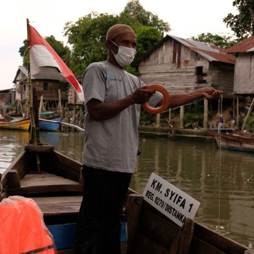 Man with jigger catching squid in Indonesia off side of boat