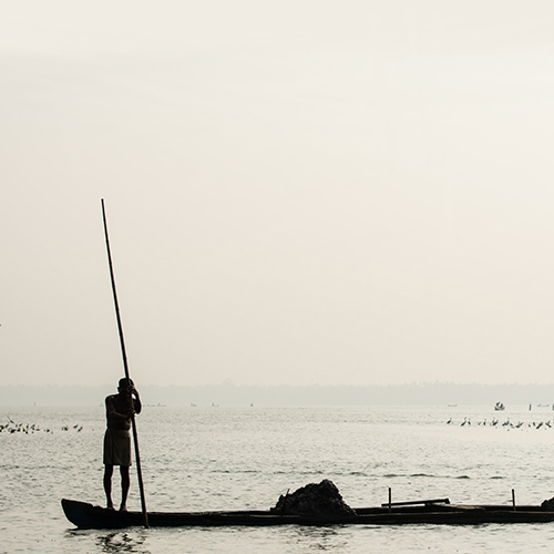 Clam fisherman standing in silhouette on small boat, India