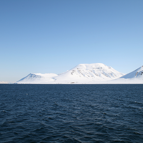 Mountains covered in snow rising out of the choppy blue Barents Sea