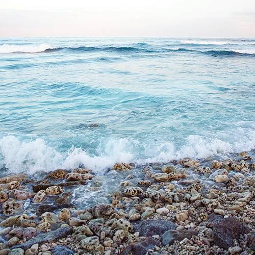 Waves crashing on stony beach, Maldives