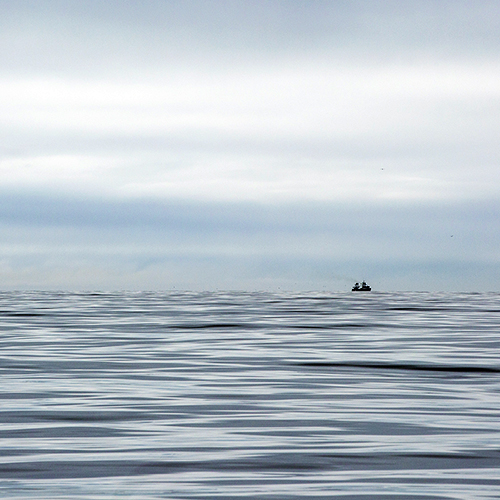 Boat on horizon on calm sea