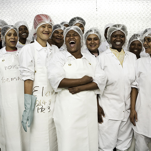 Long shot of a group of female processors in full uniform laughing