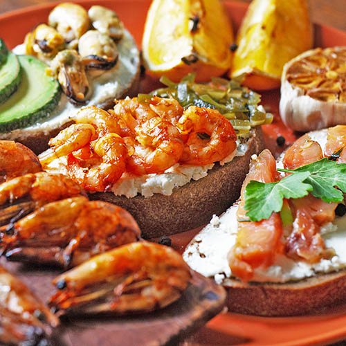 """""""Seacuterie"""" board with prawns, shellfish, salmon and avocado on slices of bread"""