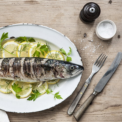 Mackerel dish (left) on a wooden table with utensils and salt and pepper (right)