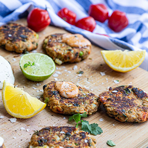Fish cakes on wooden board with lemon and lime pieces and tomatoes on tablecloth